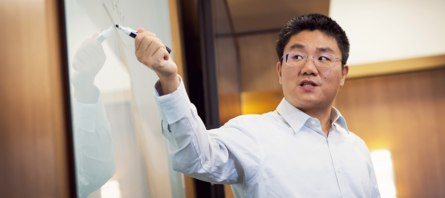 A professor pointing at notes on a whiteboard during a lecture